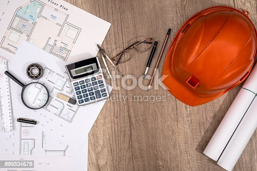 istock Construction concept - architectural project, blueprints, helmet, measuring tape 899334678