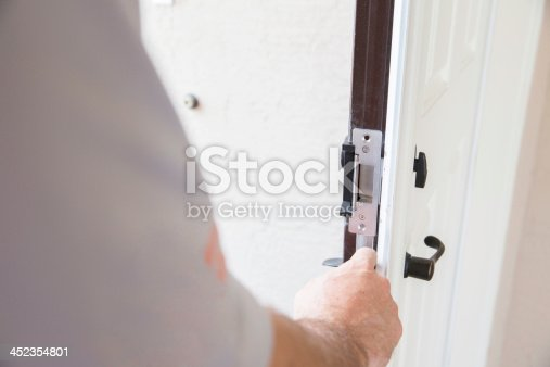 Construction: Contractor installing security lock.  rr
