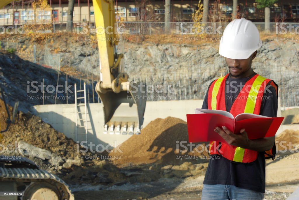 construction contractor on site reading papers shovel stock photo