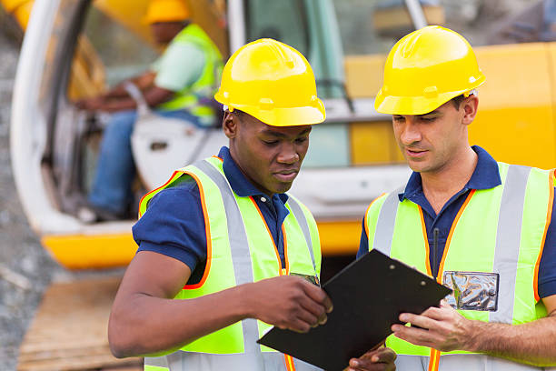 construction co-workers discussing about work plan stock photo