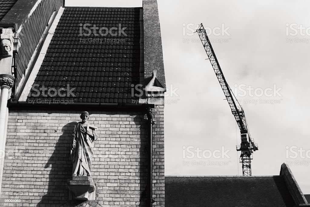 Construction Crane and Church with statue of Saint stock photo