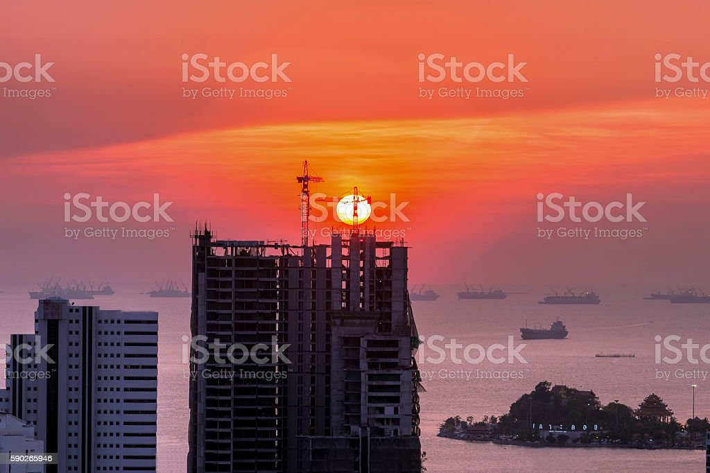 Construction crane and skyscraper in the sunset stock photo