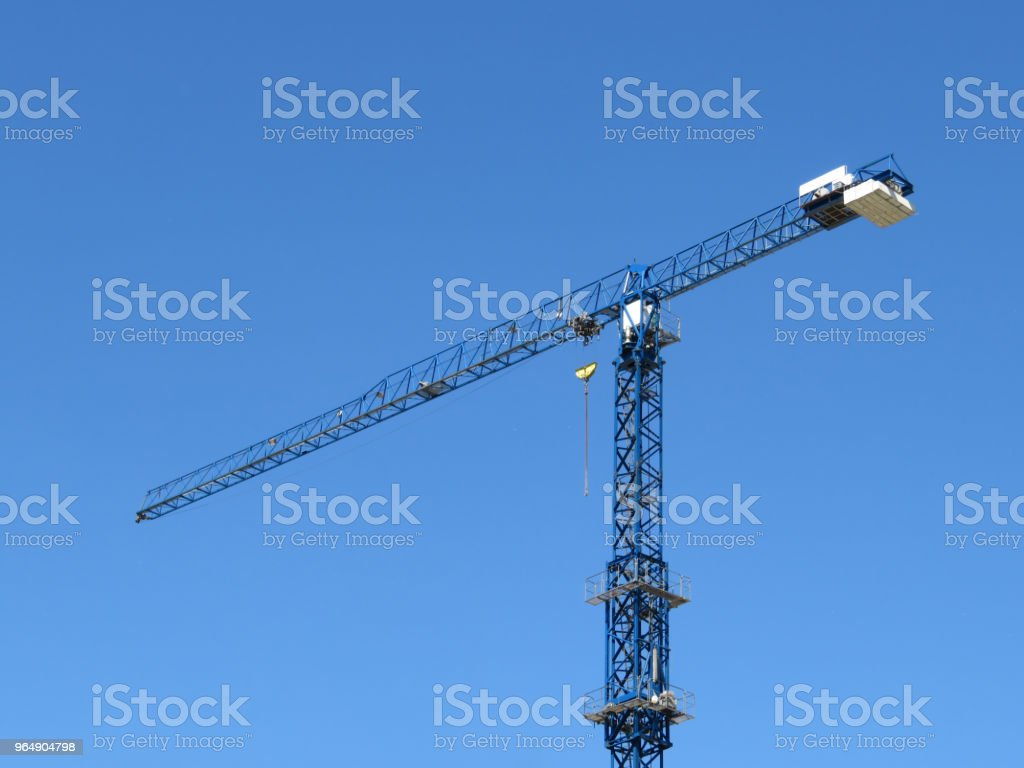 Construction crane isolated on the background of clear blue sky royalty-free stock photo