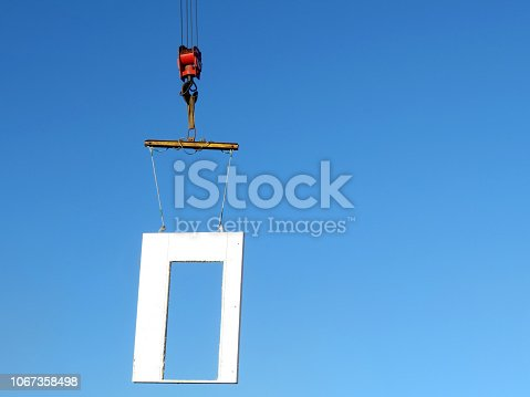Crane hook with concrete block isolated on blue sky background