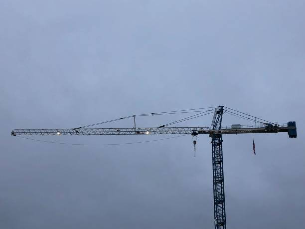 Construction Crane on a Cloudy Afternoon A construction crane hovers over a shopping complex on a cloudy afternoon. right angle stock pictures, royalty-free photos & images
