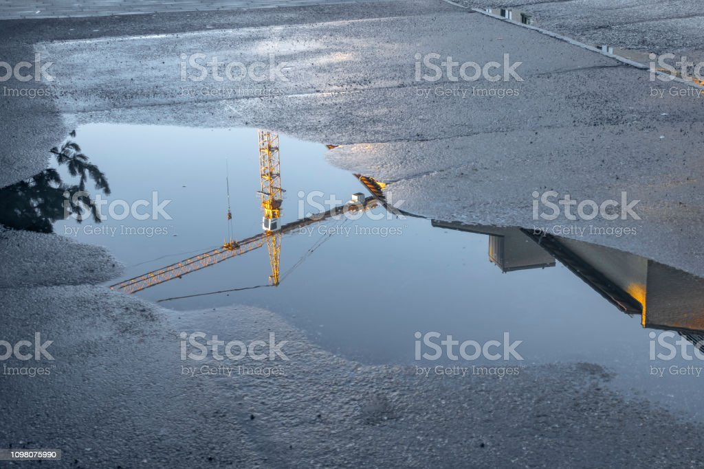 Construction crane reflected in water stock photo