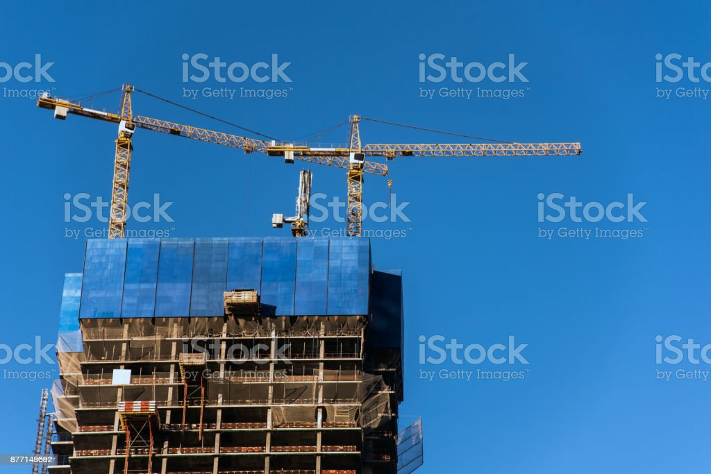 Construction cranes against blue sky stock photo