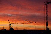 back lit construction cranes at sunrise in Cologne