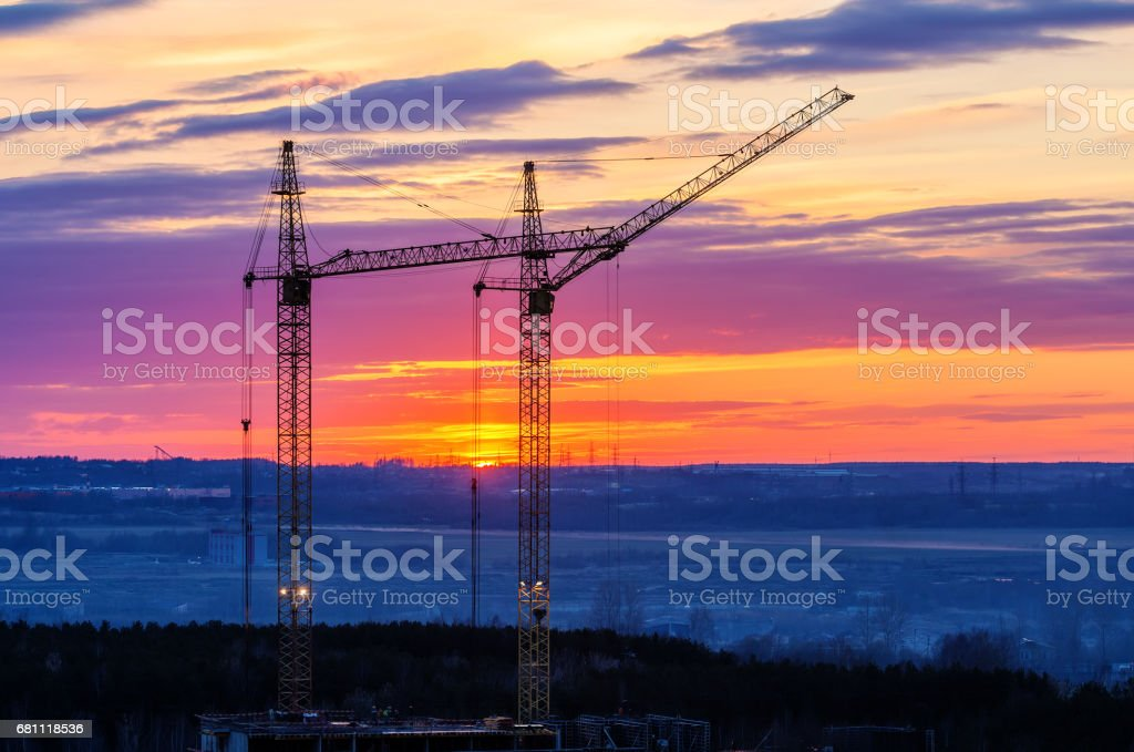 Construction cranes at sunset royalty-free stock photo