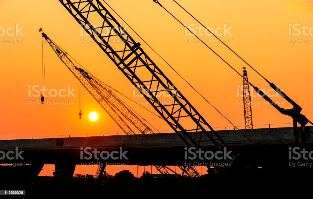 Construction Cranes Working on Bridge at Sunrise stock photo