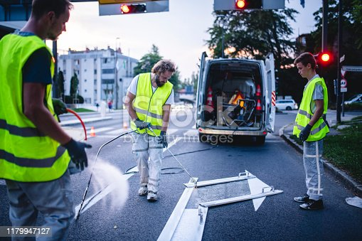 Three-man construction crew in reflective vests spray painting turn arrow marking in Central European capital city.