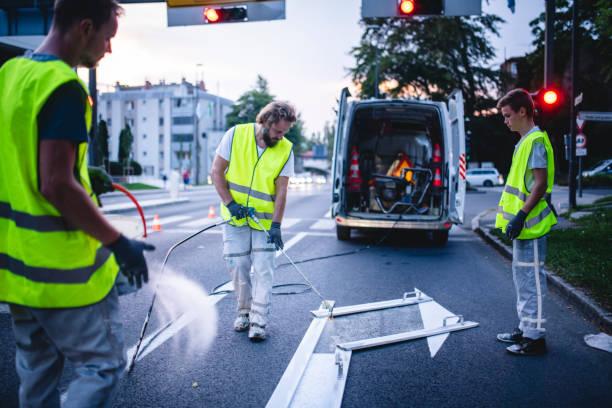 Construction Crew Mitglied Spray Malerei Turn Arrow bei Dämmerung – Foto
