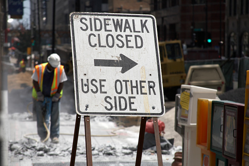 Construction crew working in background with jackhammers.  Sign in foreground reads