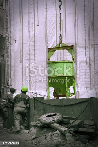 Demolition site with two construction workers. Toned image with path for the mask.