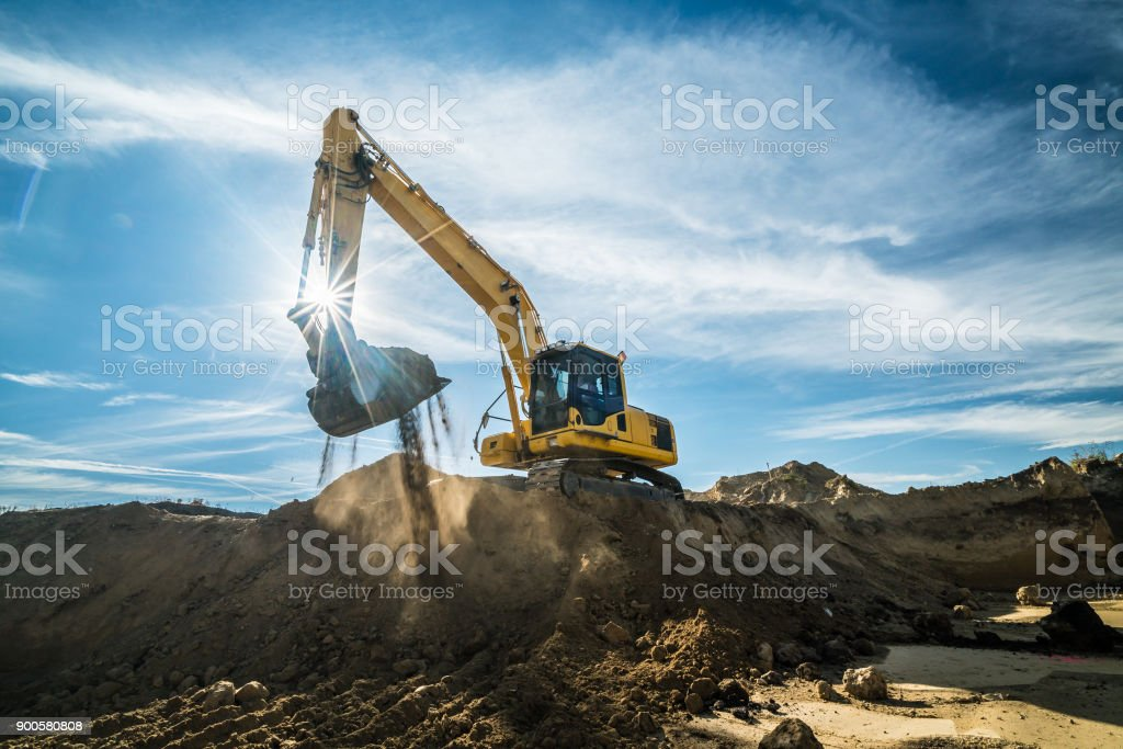 Construction - digger working at building site on sunny day stock photo