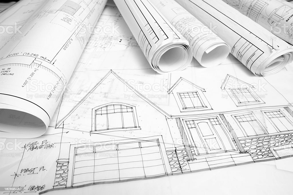 Construction drawing plans for a house rolled up together stock photo