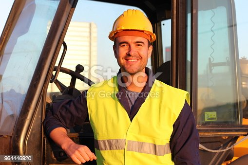 istock Construction driver with excavator on the background 964446920