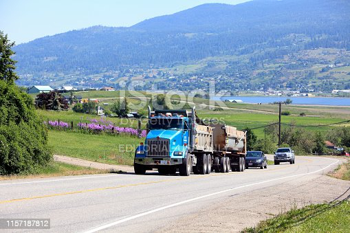 Vernon, British Columbia, Canada- May 27, 2019: Truck and two cars traveling up a rural road in Vernon BC. Swan Lake and rural properties in background.  Pink Springtime flowers.