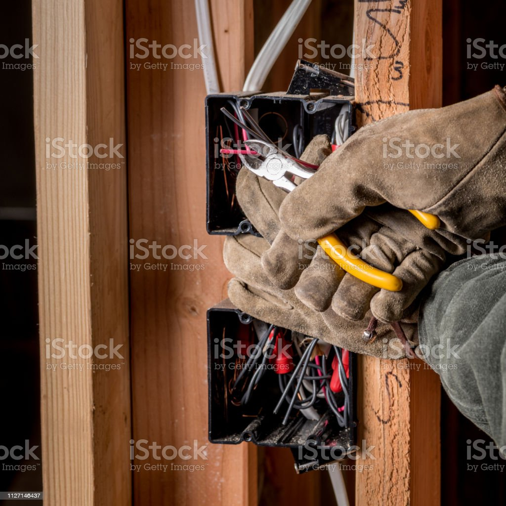 Construction Electrician Clips A Wire In New Home