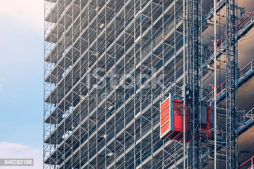 An elevator on the exterior of a tall building under construction.