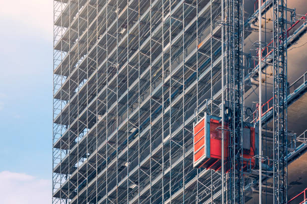 Construction elevator An elevator on the exterior of a tall building under construction. scaffolding stock pictures, royalty-free photos & images