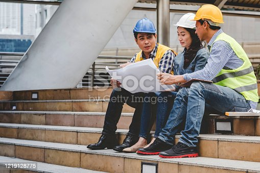 1071990712 istock photo Construction engineer in Safety Suit Trust Team Holding White Yellow Safety hard hat Security Equipment on Construction Site. Hardhat Protect Head for Civil Construction Engineer. Engineering Concept 1219128775