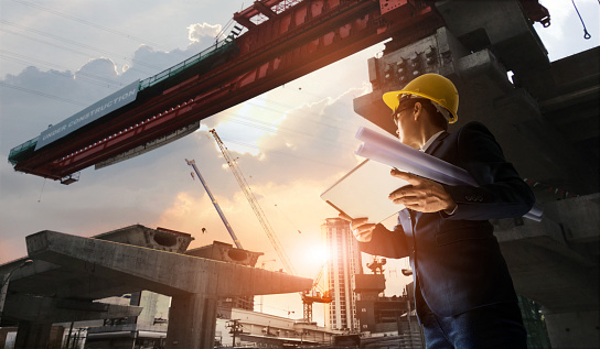 Construction engineer manager supervising progress of BTS Station Construction Project with tablet and blueprint in hands. Cranes in sunset background. Industrial technology 4.0