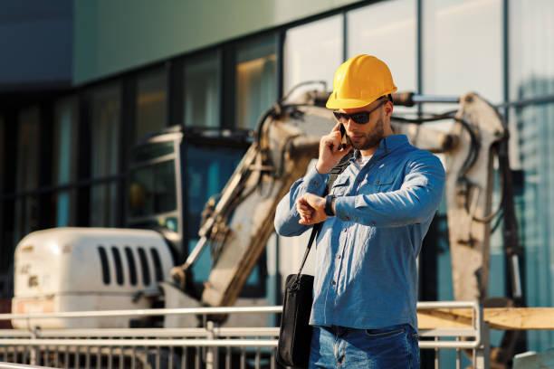 Bauingenieur telefoniert am Telefon und schaut sich die Uhr auf der Baustelle an – Foto