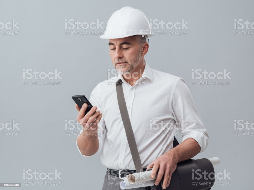 Construction engineer using a smartphone, he is connecting and text...