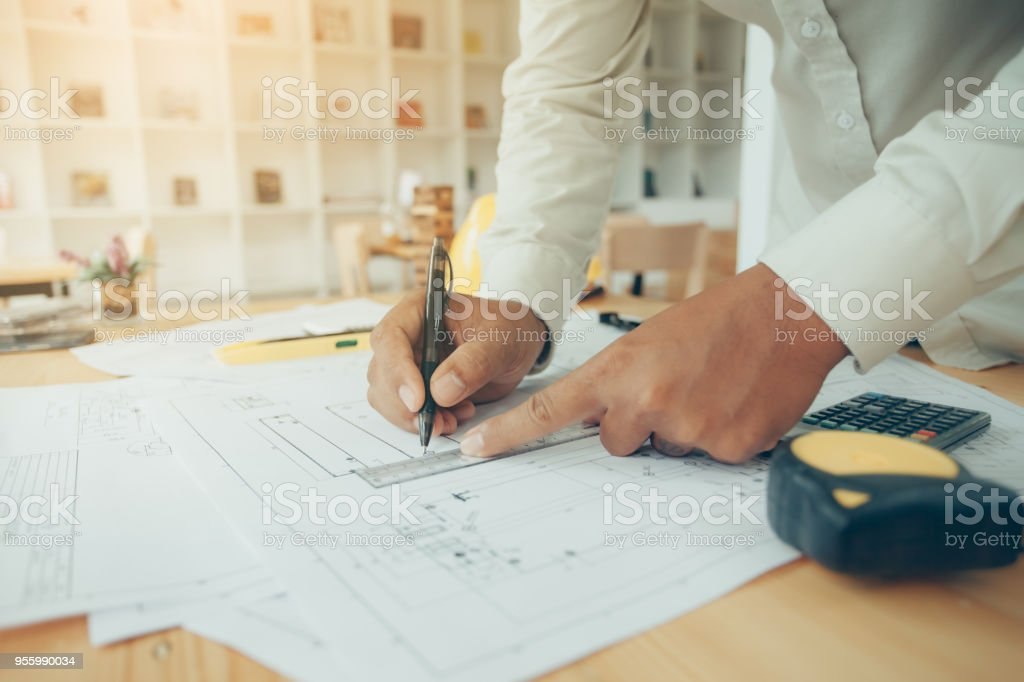 Construction engineering. Architect drawing blueprints and...