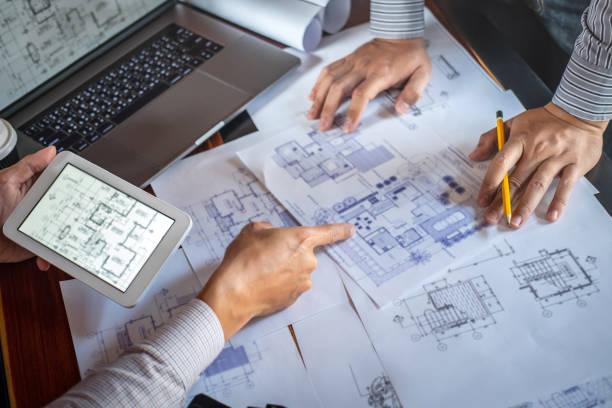ingeniería de construcción o arquitecto discutir un proyecto mientras se verifica la información sobre el dibujo y el boceto, reunión para proyectos arquitectónicos de socios - ingeniero fotografías e imágenes de stock