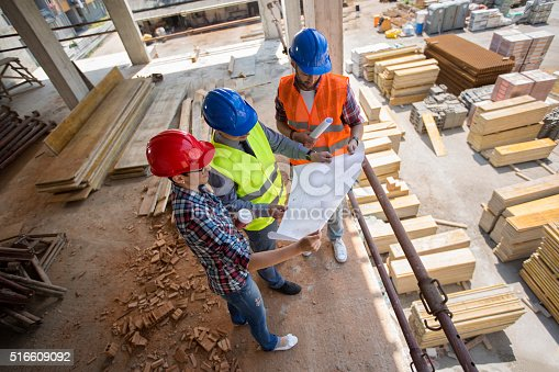 516607254istockphoto Construction engineers checking blue print at building place 516609092