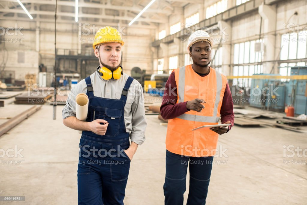 Construction engineers discussing building plan stock photo