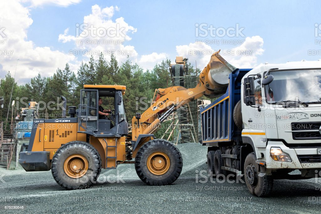 Construction equipment and machinery, a pile of construction gravel, yellow digger loads crushed stone into dumper truck tipper stock photo