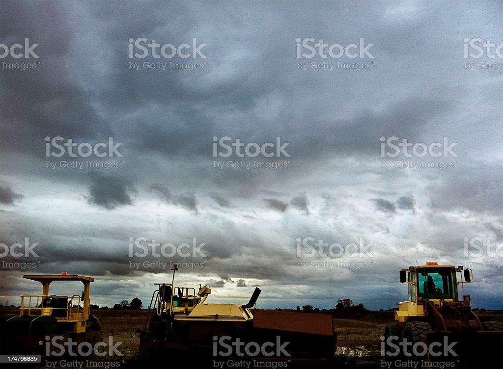 Construction Equipment Under A Dark Stormy Sky royalty-free stock photo