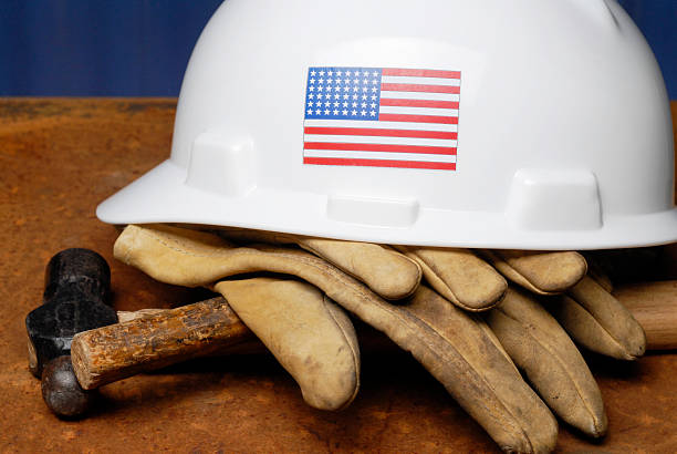 Construction essentials in American labor Stock Photograph of hard hat with U.S. flag and gloves.  labor union stock pictures, royalty-free photos & images