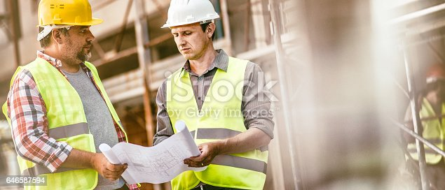 istock Construction foreman consulting an architect on construction site 646587594