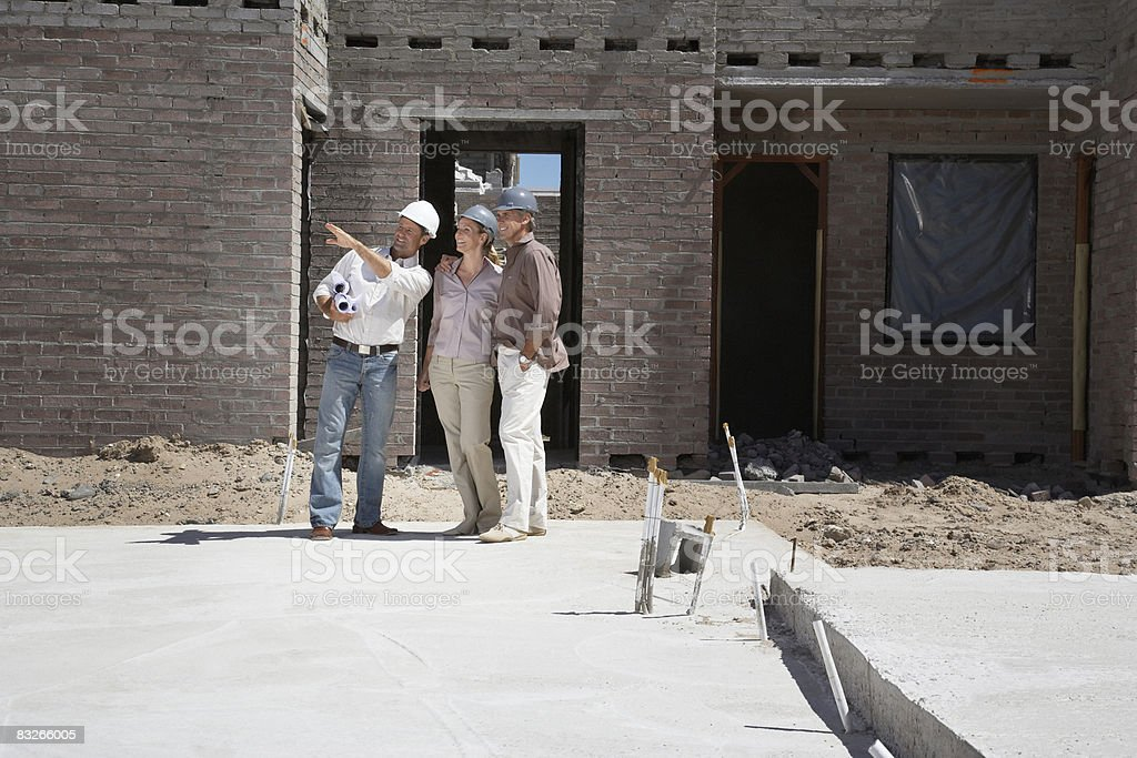 Construction foreman explaining progress to couple royalty-free stock photo