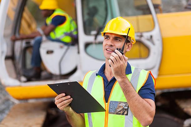 construction foreman talking on walkie-talkie stock photo