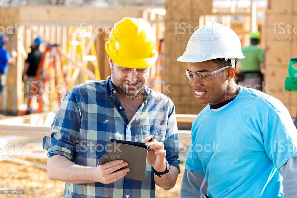 Construction foreman uses digital tablet stock photo
