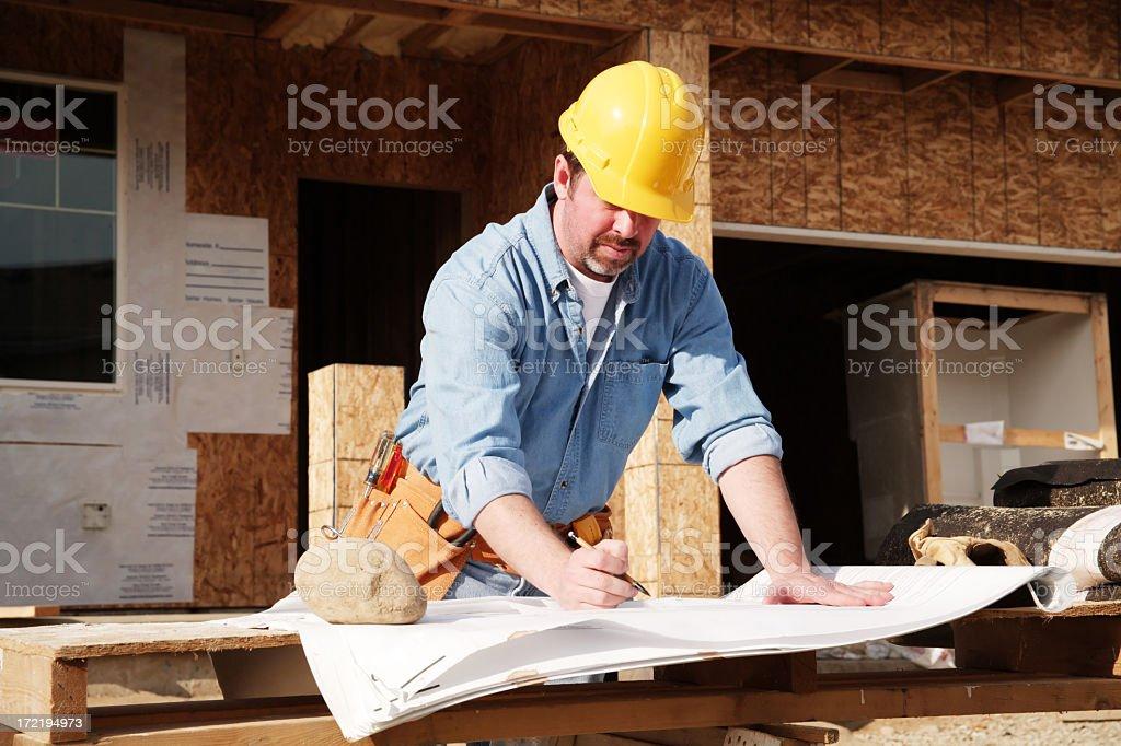 A construction foreman verifying progress on the plans stock photo