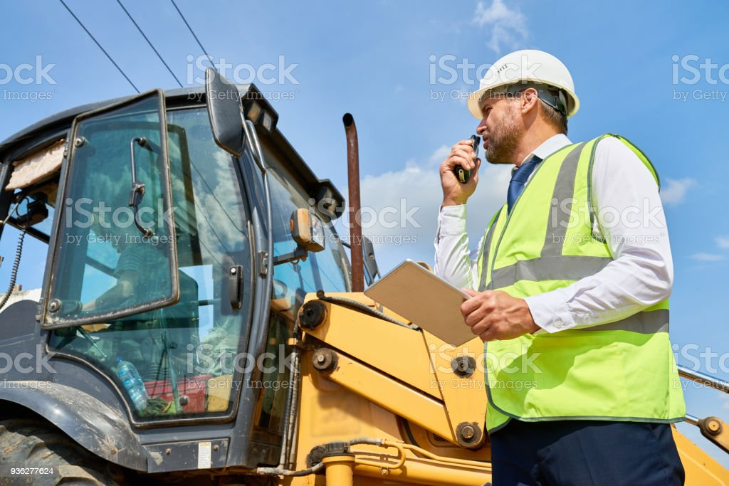 Construction Foreman Working on Site Side view portrait of businessman wearing hardhat and reflective jacket talking via portable radio set standing by road roller and using digital tablet Adult Stock Photo