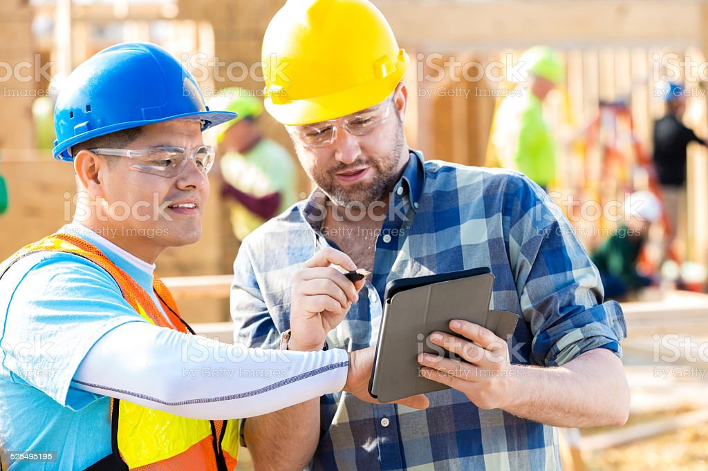 Construction foremen review plans on digital tablet stock photo