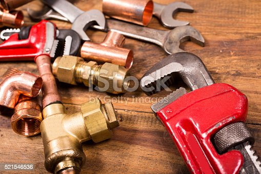 Various construction, DIY, plumber's hand tools and copper and brass plumbing pipes and fittings lie on a rustic wooden table, desk or workbench.  Tools include styles of various wrenches. Home improvement, plumbing, construction themes.  Great background.  Close up.