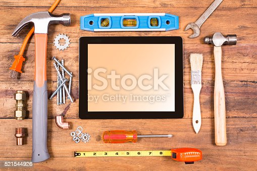 istock Construction hand tools surround a digital tablet. 521544926