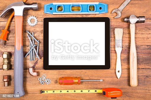 istock Construction hand tools surround a digital tablet. 521607138