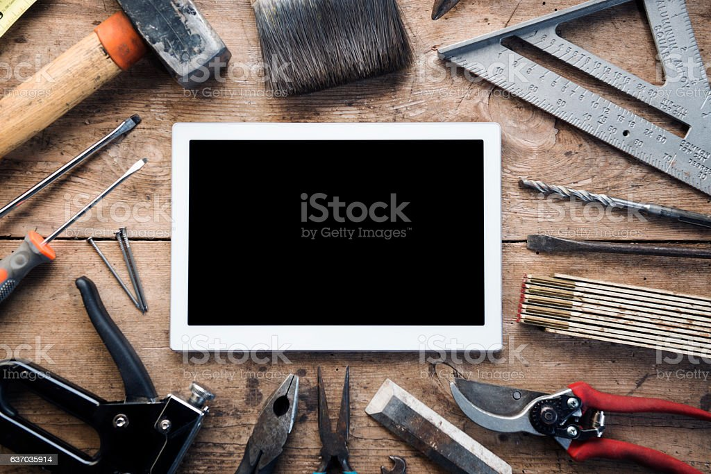 Construction hand tools surround a digital tablet stock photo