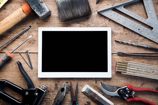construction hand tools surround a digital tablet - werkzeuge stock-fotos und bilder