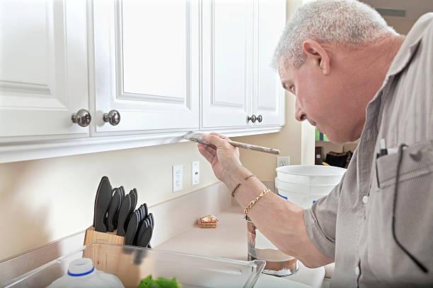 Construction: Handyman painting cabinet trim stock photo