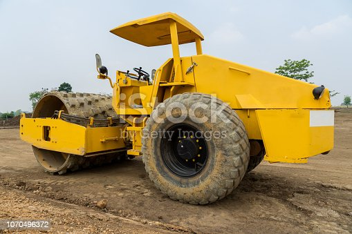 Vibratory sheepfoot compactor working on new road construction site. Heavy machinery for earth work in construction industrial.
